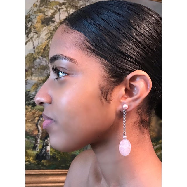 Sterling silver clip-back earrings with pale pink carved oval rose quartz drops, hanging from sterling silver link chains...