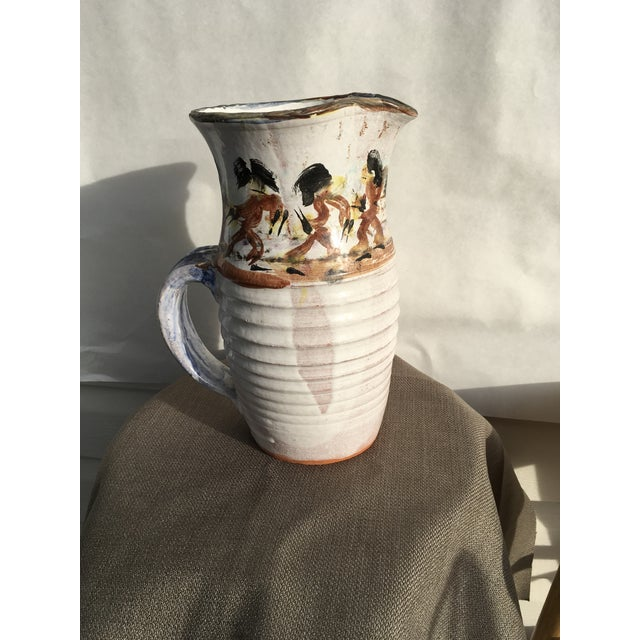 Studio hand painted pitcher with tribal dancers around the top of a white washed finish on red clay. Has a large blue...