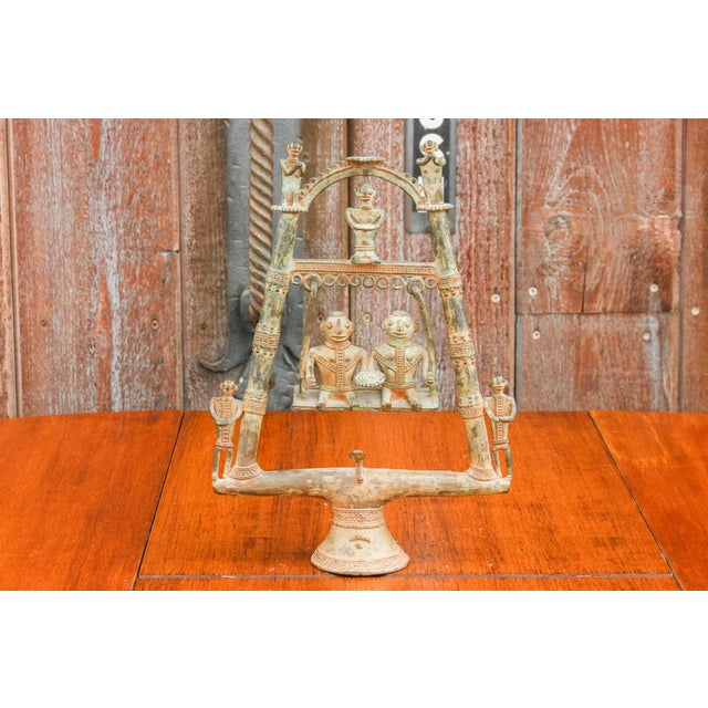 A unique piece, this tribal statue features Bastar figures seated on a swing, two guarding figures along the bottom, three...