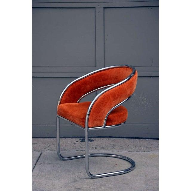 Unique 70's orange velvet and chrome armchair. Unusual banded back design.
