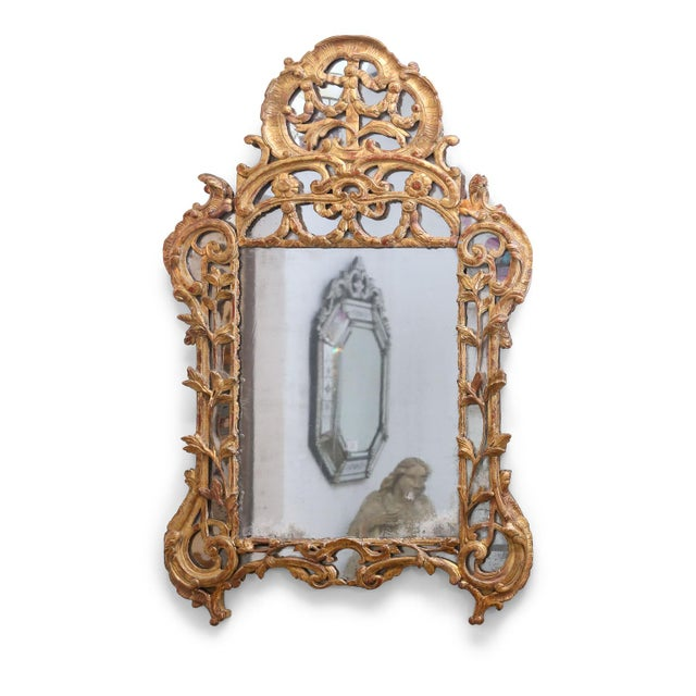 Regence period giltwood mirror circa 1720-1730. This 18th century French mirror is finely carved with original (or very...