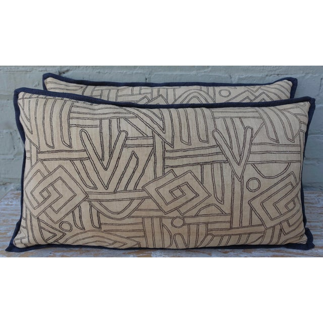 A pair of geometric Kuba Cloth Pillows. Each pillow has a different frontal pattern. Black and natural colored raffia...