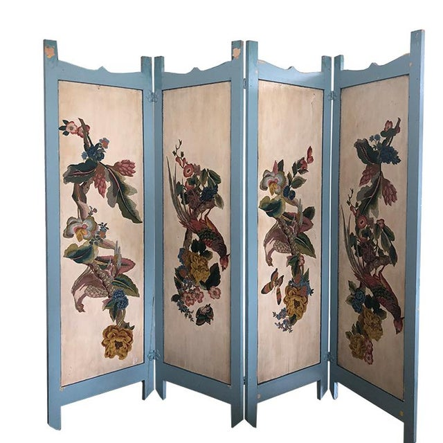 Folding divider screen featuring colorful birds and flora on the front side. The back is upholstered in cloth and trimmed...