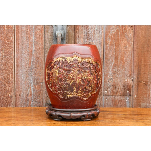 Hand carved barrel container that sits on a rosewood stand. Beautifully carved and painted in gilt with a scene of a Shou...