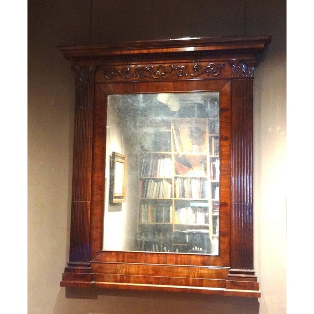 An architectural overmantle mirror in mahogany with fluted pilasters and finely carved details, possibly Viennese. Circa 1835