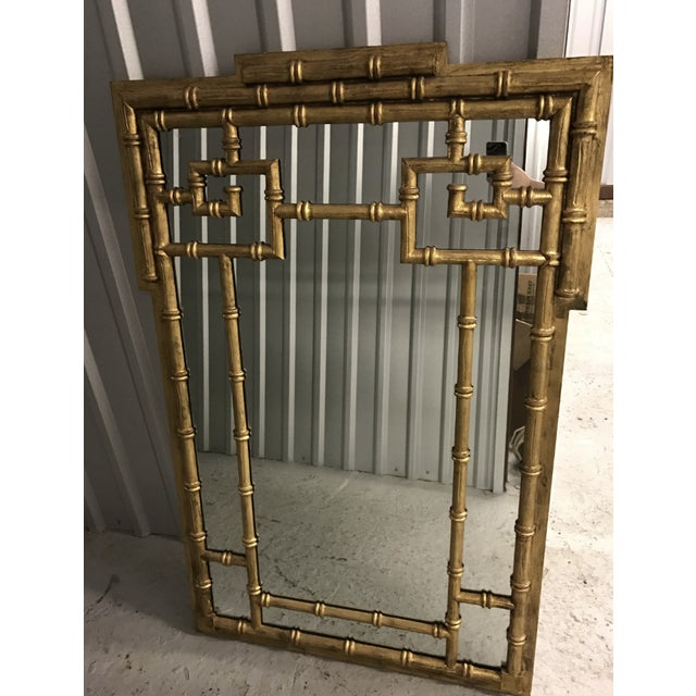 A fabulous mid-century gilded faux bamboo framed mirror, made of wood with a gold finish. This mirror features a Greek key...