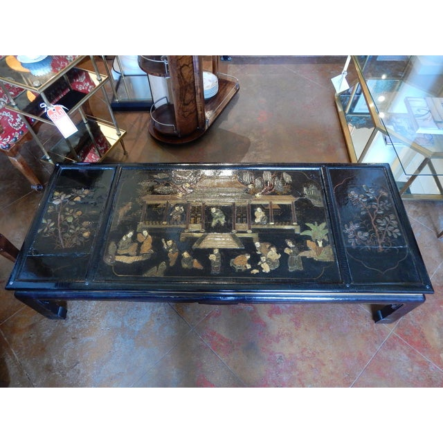 Lovely 19th century black lacquered chinoiserie coffee table. Very nice raised relief figures and scenes. Protective glass...