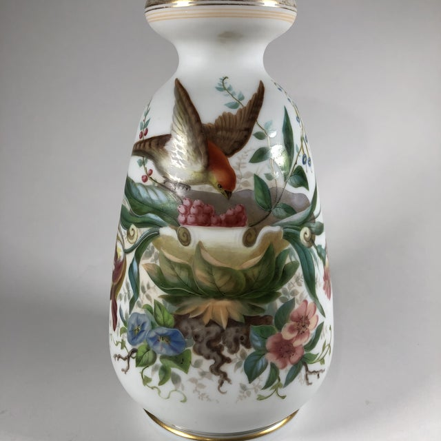 A hand-painted white opaline glass vase decorated with birds, plants, and insects. The glass body has alternating satin...
