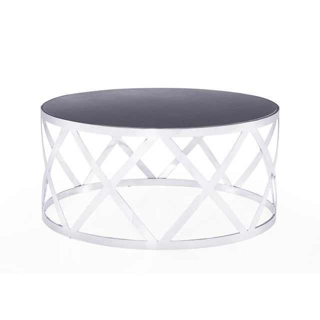 Modern drum coffee table with seamless lattice design in luminous stainless steel and accented by an encased ceramic top.
