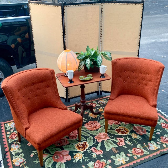 A pair of coral/burnt orange tweed lounge chairs in what is believed to be the original upholstery. Chairs are in great...