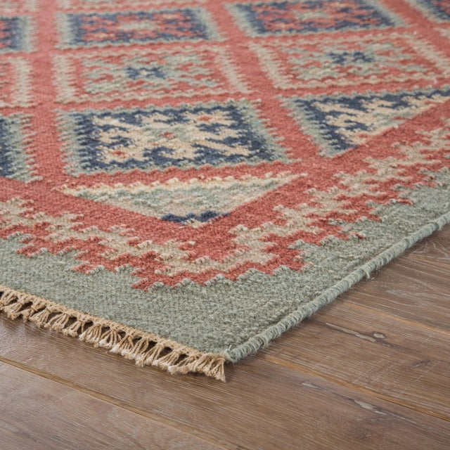 This traditional-style kilim area rug boasts a geometric diamond design in a striking blue and red colorway. The flatweave...