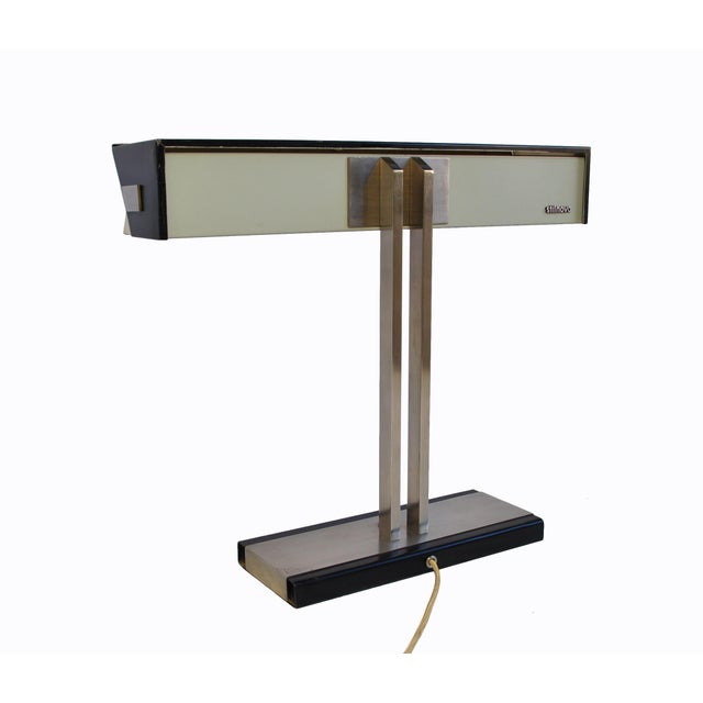 A smartly designed desk lamp from Stilnovo, Italy 1960's. The white visor can be adjusted so as to increase or decrease...