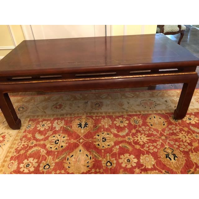 Asian-style wood coffee table in excellent condition. Reddish-brown with gold trim. Perfect size coffee table for living...