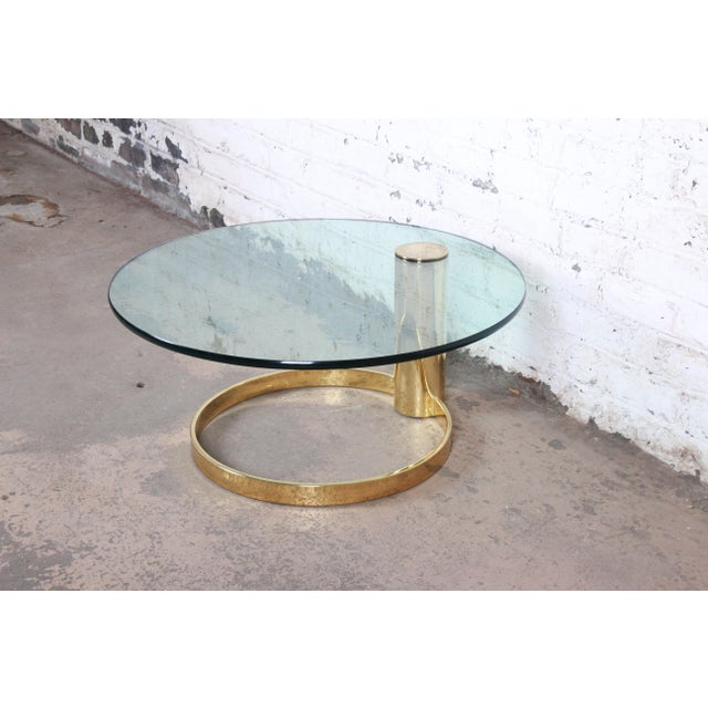 An exceptional mid-century modern Hollywood Regency brass and glass coffee table designed by Leon Rosen for the Pace...