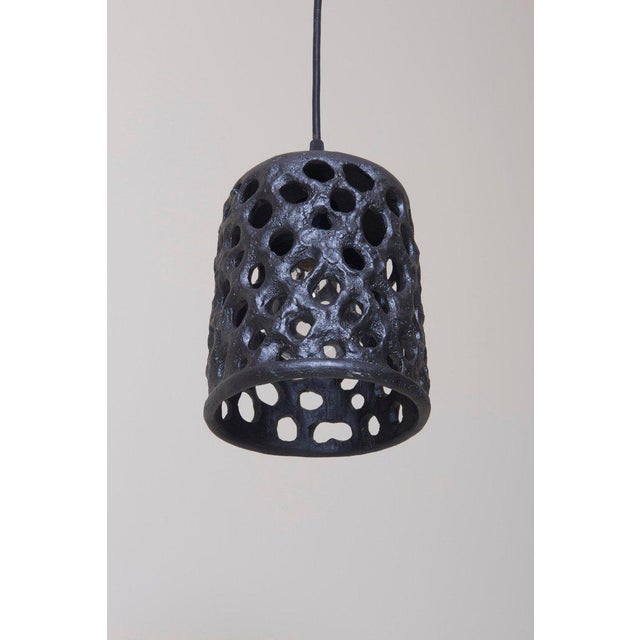 This black lantern in glazed ceramic is handmade by Stan Bitters. Warm light soaks through the different openings. One...