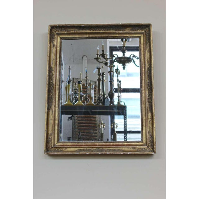 French Neoclassical style mirror with an elaborate gilt frame and original mercury mirror.