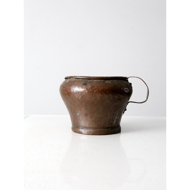 This is an antique copper spoutless pitcher. The hammed copper jug pot has a copper handle and curled rim. Beautiful age...