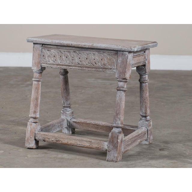 The beautifully weathered surface of this antique English limed oak joint stool circa 1890 gives it a wonderfully...