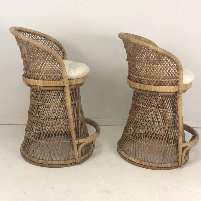 A pair of woven rattan and wicker barstools. Cream colored seat cushion in great condition.