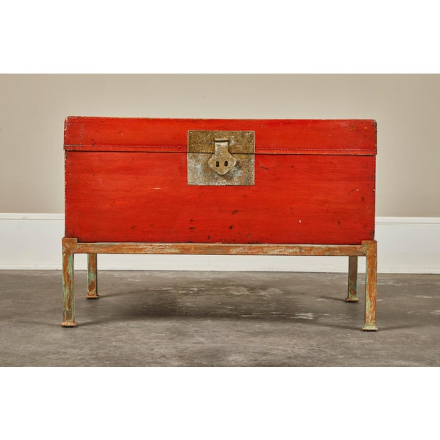 A 19th century pig-skin leather camphor trunk on newer stand. Red lacquer finish with front latch and side handles.