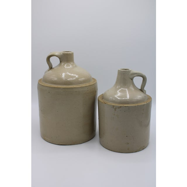 A set of 2 American stoneware jugs. These antique utilitarian pieces are beautiful statements on a kitchen shelf,...