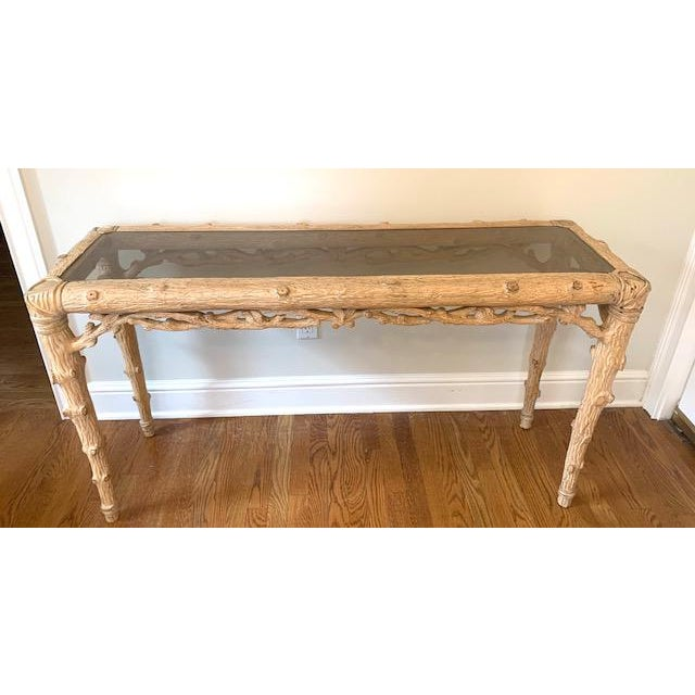 Faux bois carved wood console table. Lovely detail, lightly smoked glass top. Pale Bleached finish. From an estate in the...