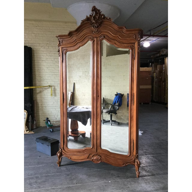 Stunning Louis XV-style armoire. Made of walnut, this armoire features double mirrored doors, and a beautifully carved...