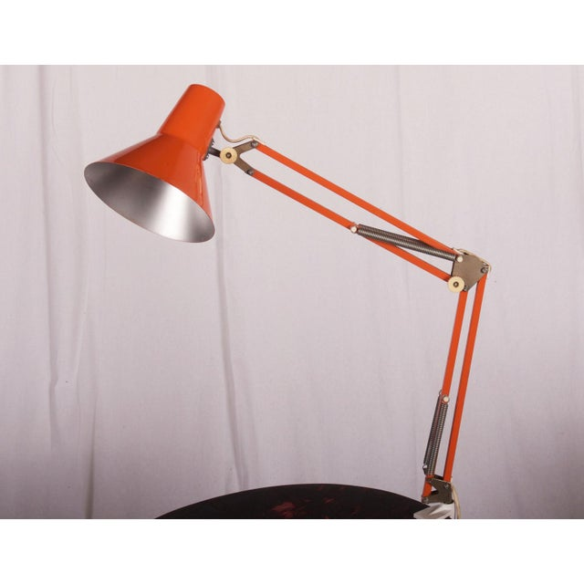 This lamp is attached to the side of a desk was produced by Luxo in the 1970s. It is made of orange lacquered steel and is...