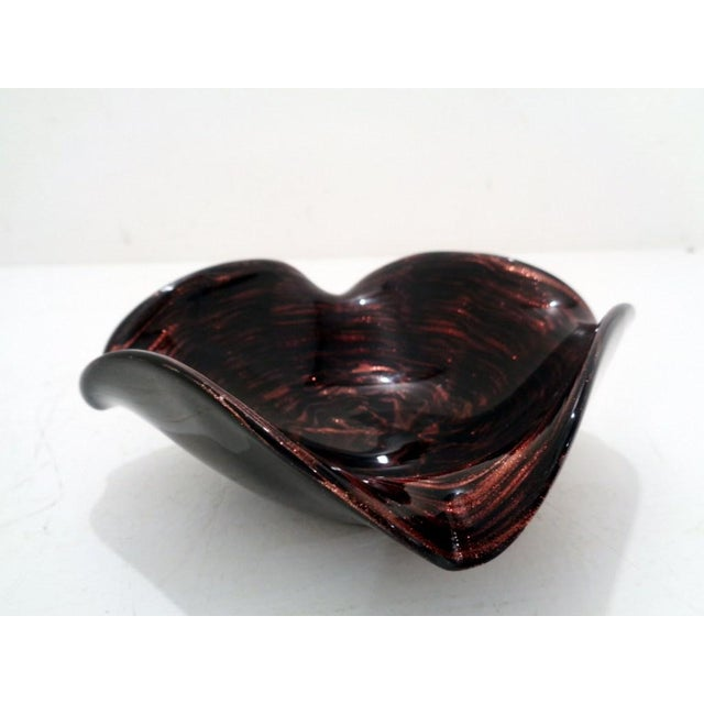 Lovely 1950's Venetian free form art glass dish made in Murano, Italy. Dark/black amethyst color with copper red color and...