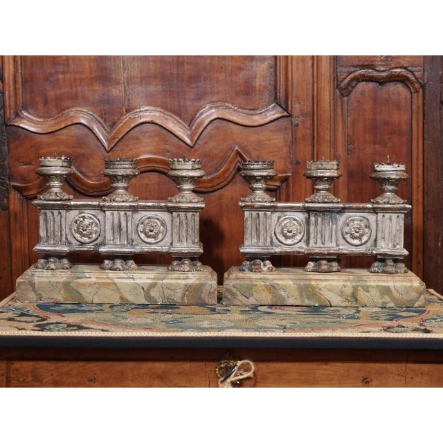 Three candle holders over a silver leaf carved base standing on 3 claw foot over a faux painted marble rectangular base....