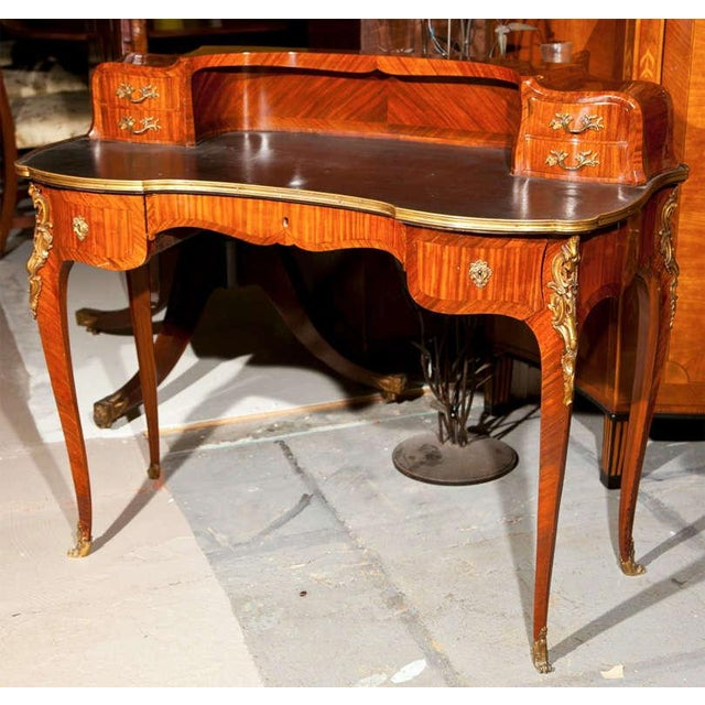 An exquisite French Rococo style rosewood writing table, early 1900s, the leather writing surface with bronze banding...