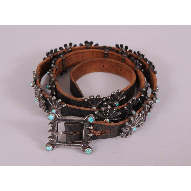 Twenty three sterling and turquoise conchos and a matching belt buckle are attached to a black leather belt for a striking...
