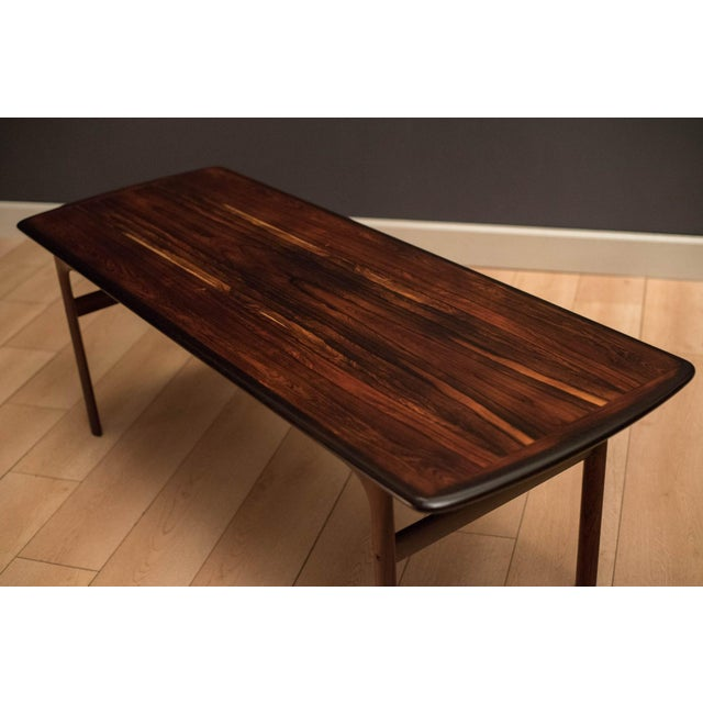 Mid-century modern coffee table manufactured by Westnofa of Norway. Table top features gorgeous rosewood grains wrapped...
