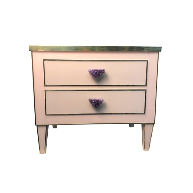 The Lillian nightstand is a delicate creation made of back-painted glass. Hand formed brass detailing and a large amethyst...