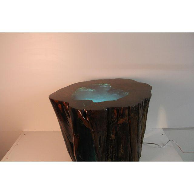 A hollow tree stump is filled with verdant green-hued translucent resin in this unique organic modern side table;...