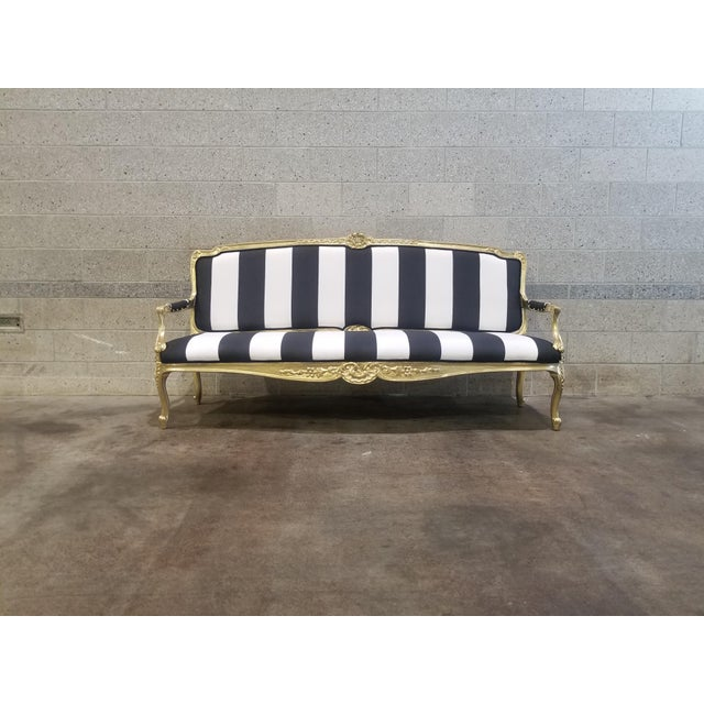 Stunning vintage settee. Frame professionally refinished in gold. Professionally upholstered in black and white stripes....