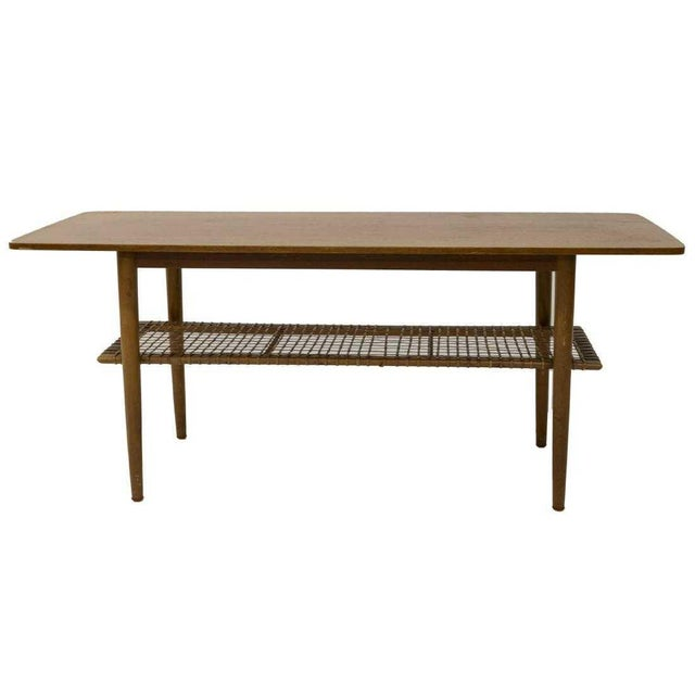 Super retro Danish mid-century modern teak coffee table, c. 1950s. Features a rectangular top over a woven cane medial...