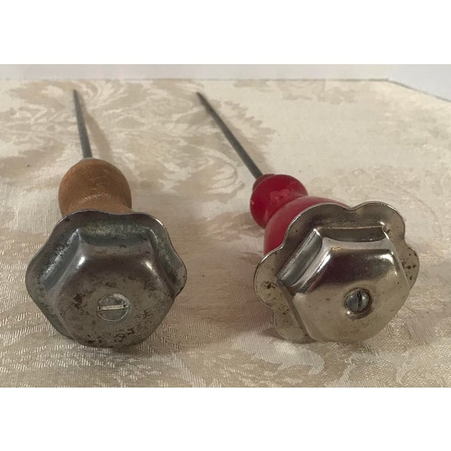 Nice pair of wood Handle ice picks with metal end caps. One is Red and the other is natural.