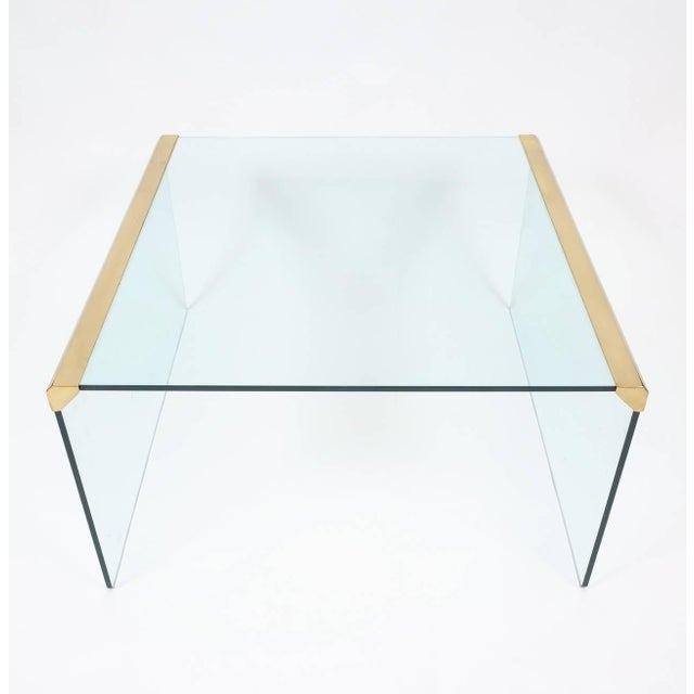 "Well sized 31"" x 31"" clear glass and brass coffee table by Pierangelo Galotti for Galotti & Radice in excellent condition."
