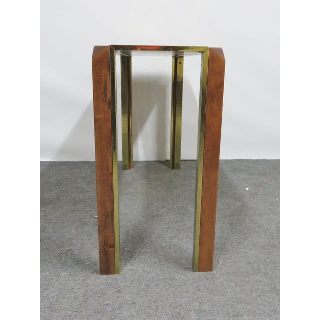 This is a vintage mid-century brass console table with burlwood top, solid maple legs