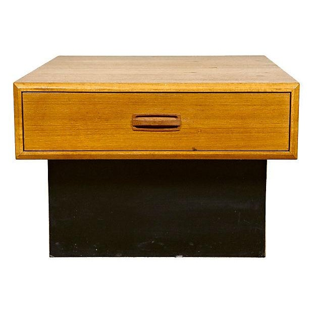 Teak wood coffee or side table with a black painted base. Circa 1960s. Has a single drawer for storage. Light wear to paint.