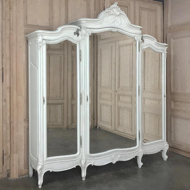 19th Century French Louis XV Painted Triple Armoire features a triple compartment design with the center section stepped...