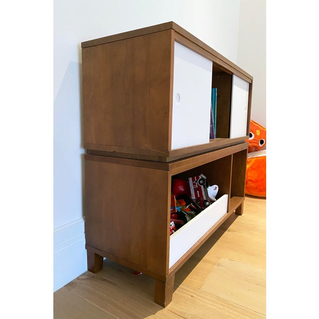 Walnut stained wood stacked bookshelf and toy box with angled feet at base. White painted sliding doors a shelf accent....