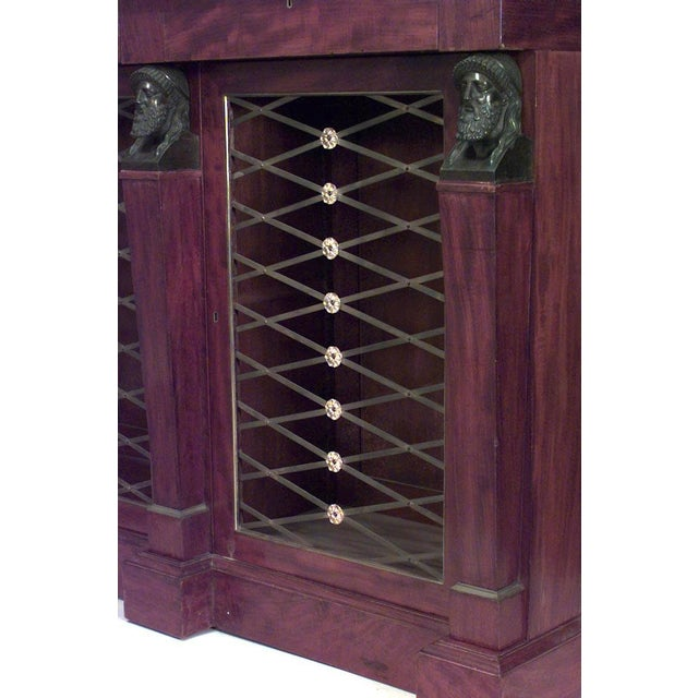English Regency mahogany bookcase with eight brass lattice doors and bronze classical Grecian heads.