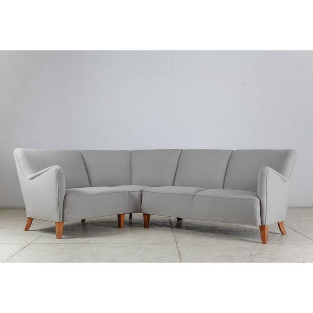 A large Danish corner sofa standing on eight stained beech legs and upholstered with a light grey wool. The sofa can be...