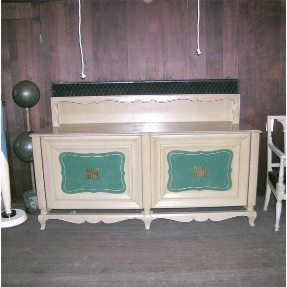 Two green leather insert doors with two large, shaped brass knobs. Buffet has a light wood finish.