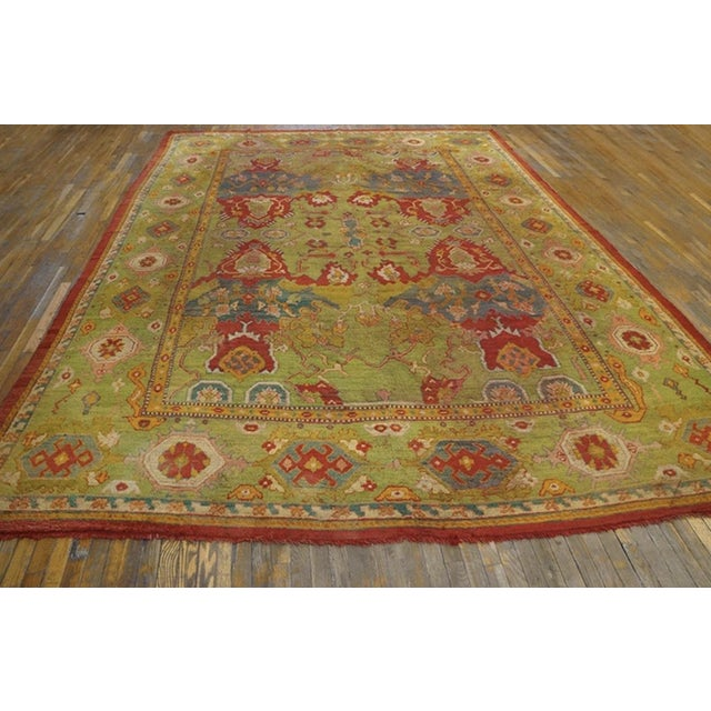 Antique Oushak Rug with a green background.