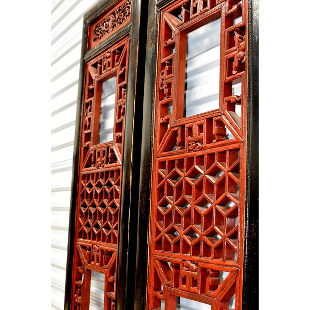 A pair of beautiful Chinese Antique screens in black and red lacquer. The main openwork was created using the painstaking...