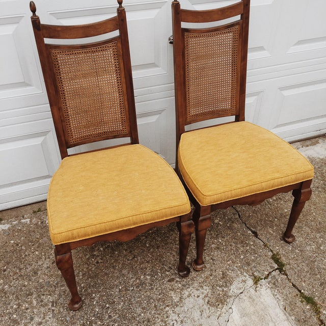 Pair of wood cane dining chairs with mustard yellow upholstered seat cushion. Cane, wood and upholstery looks great!...