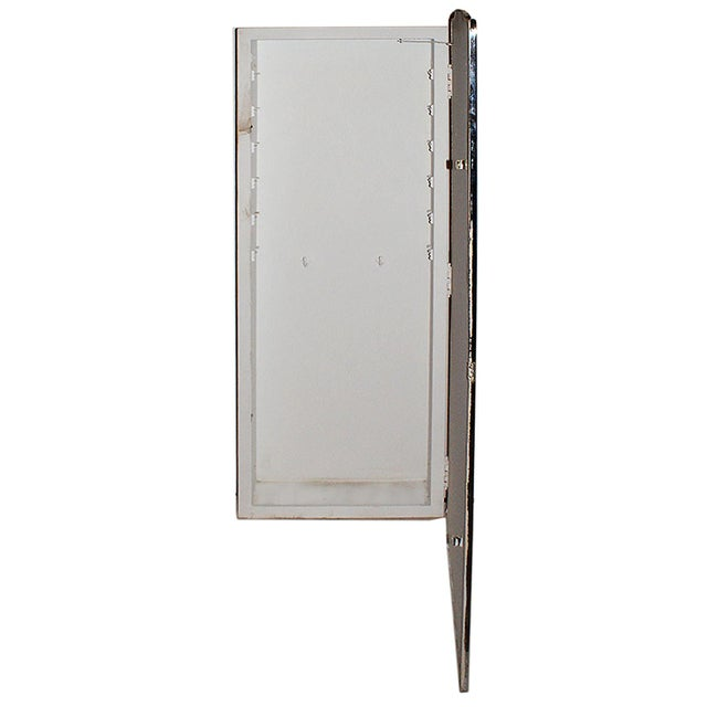 Late 20th century chrome frame wall inset medicine cabinet of long form having reverse cut border design.